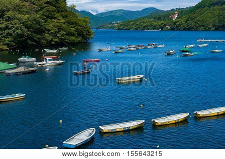 Fisherman On Wooden Boat On Ashi Lake On Sunny Day