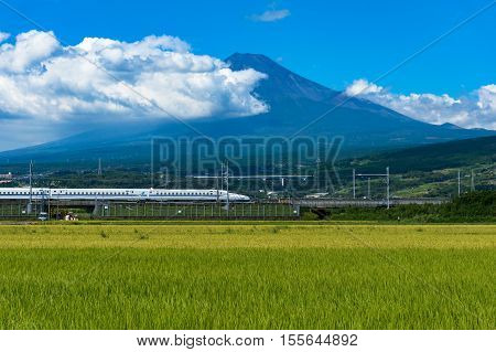 Shizuoka prefecture Japan - September 3 2016: Bullet train Tokaido Shinkansen express travels on Japanese countryside with iconic Mount Fuji volcano on the background. Iconic Japan sightseeings