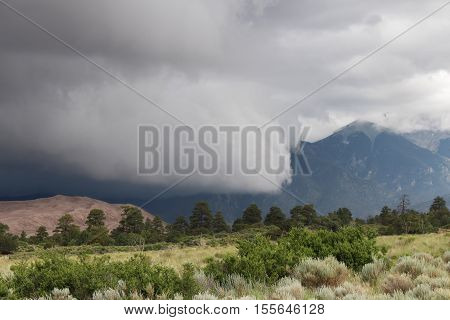 Ominous low clouds move in over sand dunes in Colorado.
