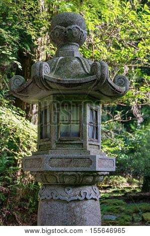 Japanese stone lantern spirit house surrounded by trees with lush green leaves