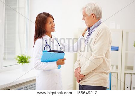 Female doctor consoling an elderly patient in office