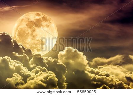Attractive photo of gold background nighttime sky with clouds and bright full moon with shiny. Nightly sky with beautiful full moon behind cloud. Outdoors at night.