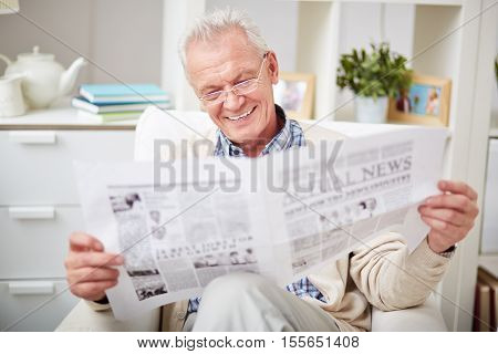 Happy senior man reading a newspaper sitting in armchair