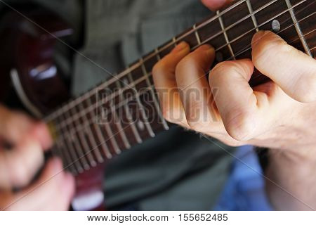 Guitarist's hand forming chord on an electric guitar.