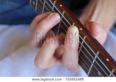 Closeup on a guitarist's hand forming a chord on an electric guitar.