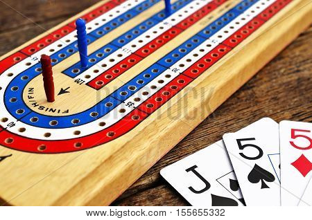 A low angle view of a wooden cribbage board and playing cards.