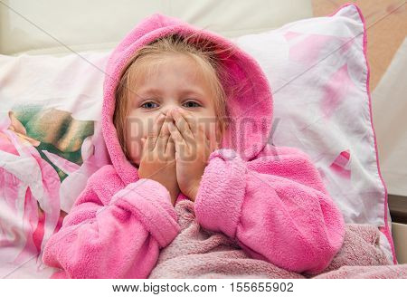 Little girl in bed in a warm bathrobe bewildered looks into the camera