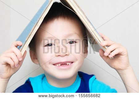 Smiling Boy With Dropped Milk Tooth With Book On Head Making Roo