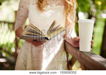 Girl reading a book and drinking coffee on wooden balcony