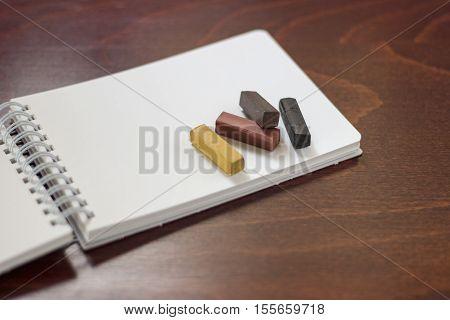 Hard pastels on the sketchbook on a wooden desk