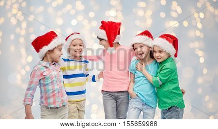 childhood, christmas, holidays, friendship and people concept - group of happy smiling little children in santa hats hugging over lights background