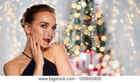 christmas, people, luxury and fashion concept - beautiful woman in black with red lips over holidays lights background
