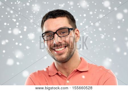 business, people, winter, christmas and eyesight concept - portrait of happy smiling man in eyeglasses over snow on gray background