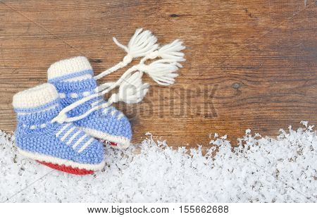 Wooden background with baby's bootees and winter snow on the border and copyspace for your Christmas text