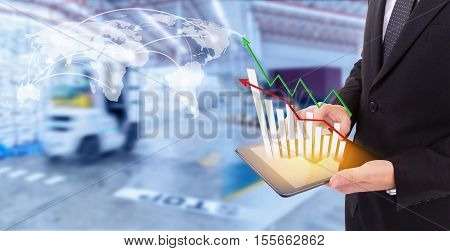 Business hand holding growth chart of transport business on tablet with goods distribution at warehouseLogistic Import Export automobile background (Elements of this image furnished by NASA)