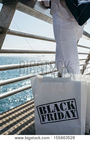 View of incognito woman standing next to Black Friday purchases on sea front border.Copy space