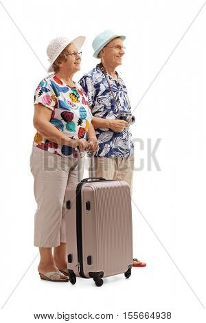 Full length profile shot of senior tourists with a suitcase waiting in line isolated on white background