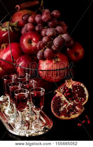 Still life on a dark background. Wine (liquor) glasses fruits and berries (apples pomegranates and grapes) in the basket.