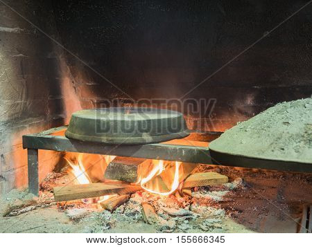 Picture of the stone bread oven stove with burning wood fire and red flames inside. Image of the burning wood fire against the background of the sooty wall.
