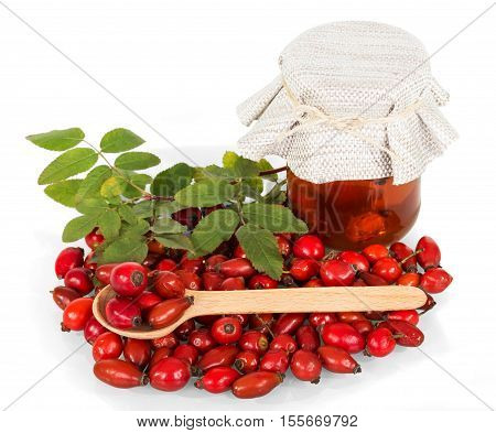 A pile of dog rose berries and a glass jar with a drink, a wooden spoon isolated on white background.