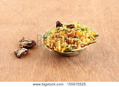Indian food tamarind rice, which is a vegetarian, traditional, popular and south Indian rice dish, in a bowl made from dry leaves.