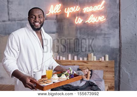 All you need is love. African young delighted man holding the tray while preparing breakfast for his wife and smiling.
