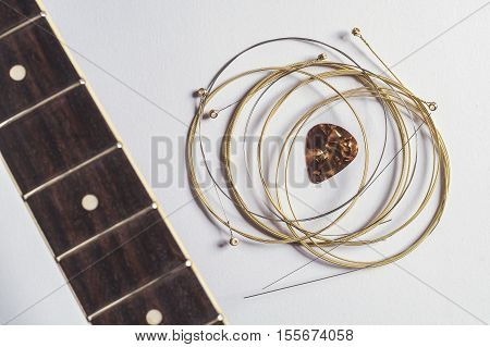 Acoustic guitar strings pick and guitar neck on gray paper background