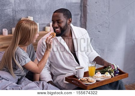 Be happy. Delighted pretty international couple feeding each other with cookies and having breakfast while lying in bed together.
