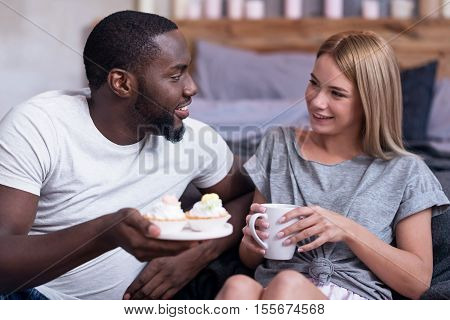 Gorgeous breakfast. Delighted young international couple enjoying cupcakes while having breakfast and sitting in bed together.