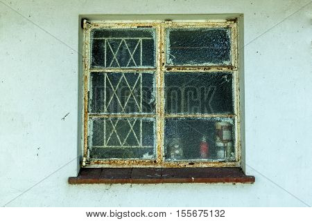 Single rusted neglected window and glass on dirty light blue wall