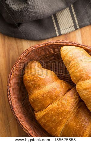 Tasty buttery croissants on wooden table. Top view.