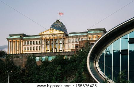 Tbilisi Georgia - October 15 2016: Part of Concert Hall against the Official residence of Georgian President in Tbilisi with illumination in the dusk Georgia