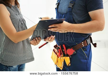 Woman writing on clipboard of worker against light background, close up view