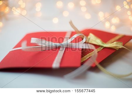 close up of two red greeting cards with ribbon bows on white background with christmas lights