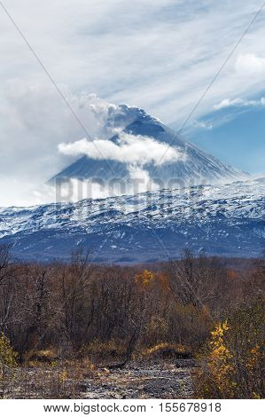Volcanic landscape of Kamchatka: active Klyuchevskaya Sopka view of volcanic eruption - plume of gas steam and ash from crater. Kamchatka Peninsula Russian Far East Klyuchevskaya Group of Volcanoes.