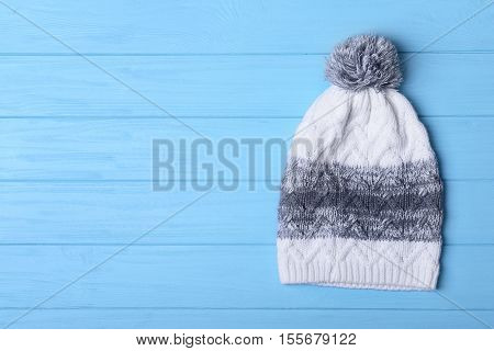 Colorful knitted cap with pompon on blue wooden background