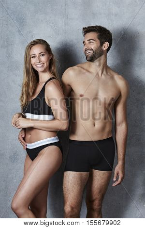 Laughing and undressed couple in studio portrait