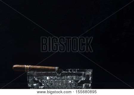 Cigar on glass ashtray against black background