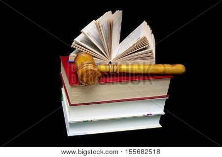 stack of books and a hammer judge on a black background. horizontal photo.