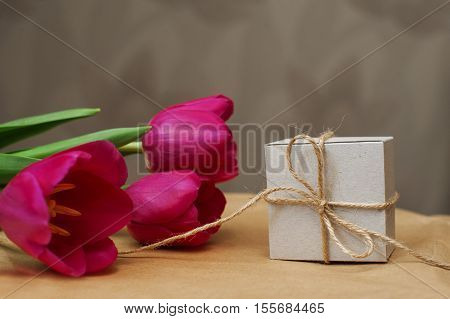 Purple tulip bouquet and gift box on wooden table with copy space.