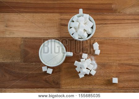 Cup of sugar powder and sugar cube on a wooden table