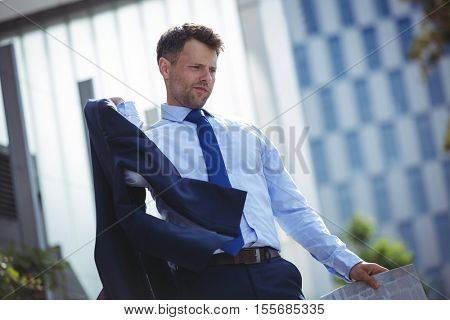 Thoughtful businessman holding blazer and newspaper near office building