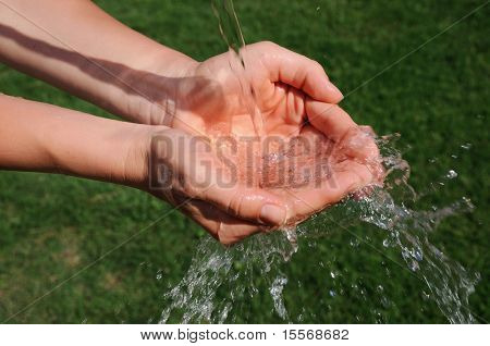 The hands of a young girl and a jet of water