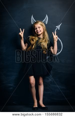 Funny little imp girl. Cute child girl posing with imp horns and tail drawn on a blackboard.