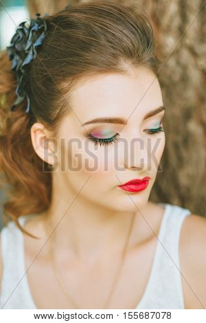 Woman with red lipstick and colored makeup, portrait in nature. Looking to the side. His eyes covered