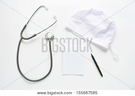 Medical stethoscope and hat with notebook on white background. Top view of doctor workplace. Diagnostic tool cardiologist, physician and therapist. Flat lay composition,