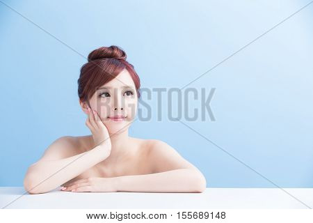 charming woman face smile and look somewhere close up while lying isolated on blue background asian girl