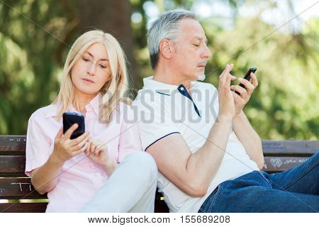 Mobile phone addiction concept - couple looking at their mobile phone while on a date