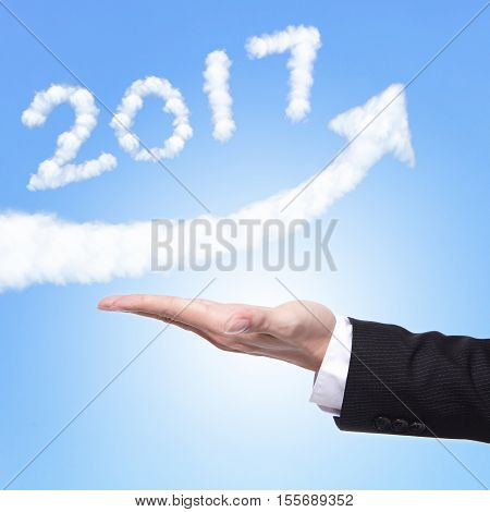 hand of Business man holding happy new year 2017 (white cloud and blue sky on sunny day) on his hand