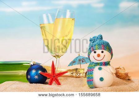 Bottle and two glasses of champagne, snowman, Christmas ball, starfish, shell in the sand against the sea.